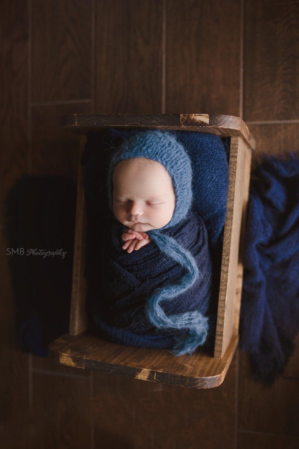 Baby boy in cradle wrapped in navy blue