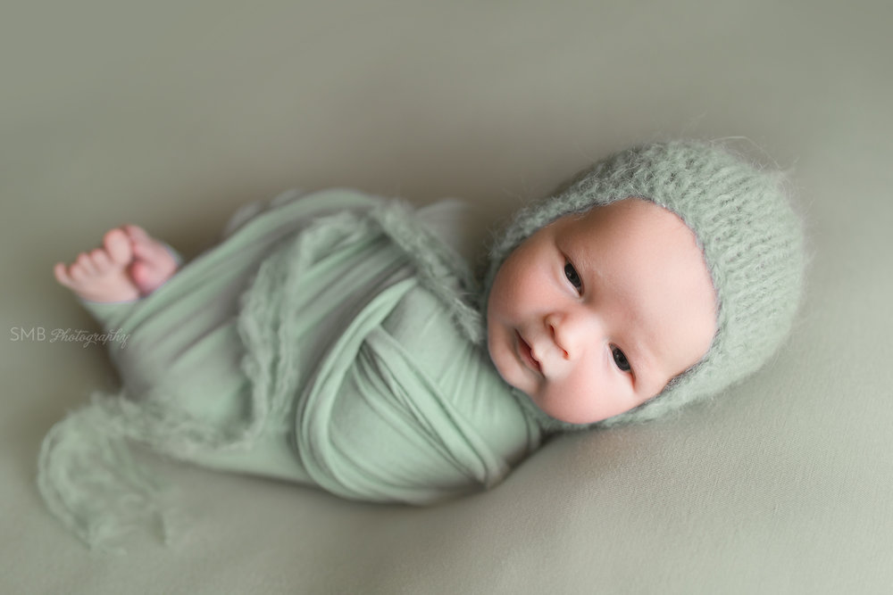 Newborn wrapped on sage green fabric wearing fuzzy bonnet