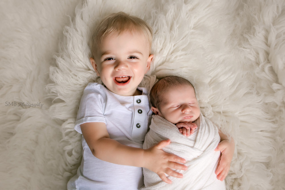 Big brother smiling holding newborn