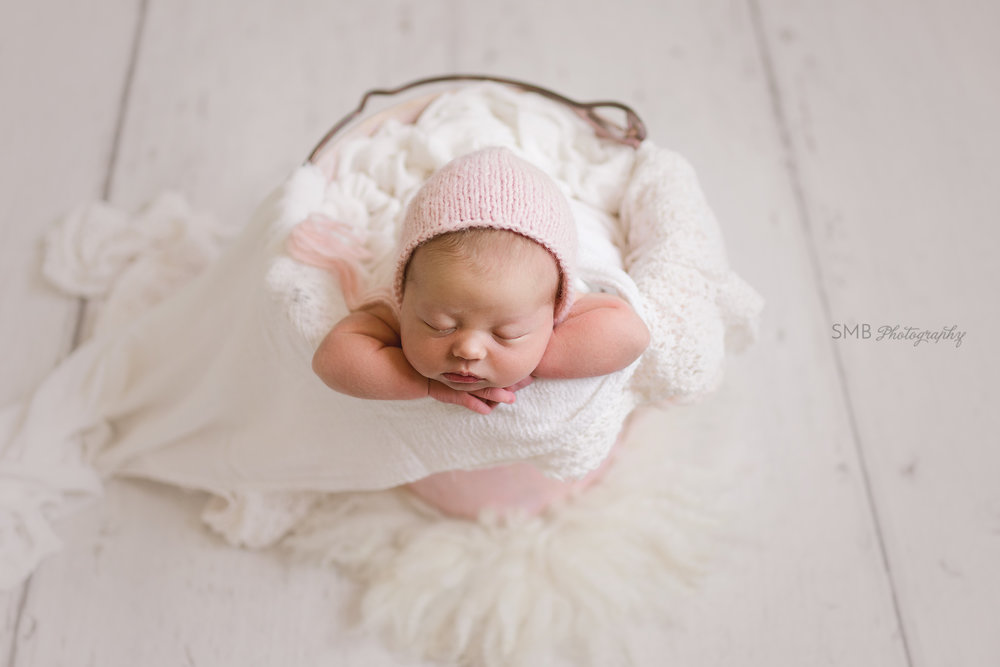 Newborn baby girl in pink bucket
