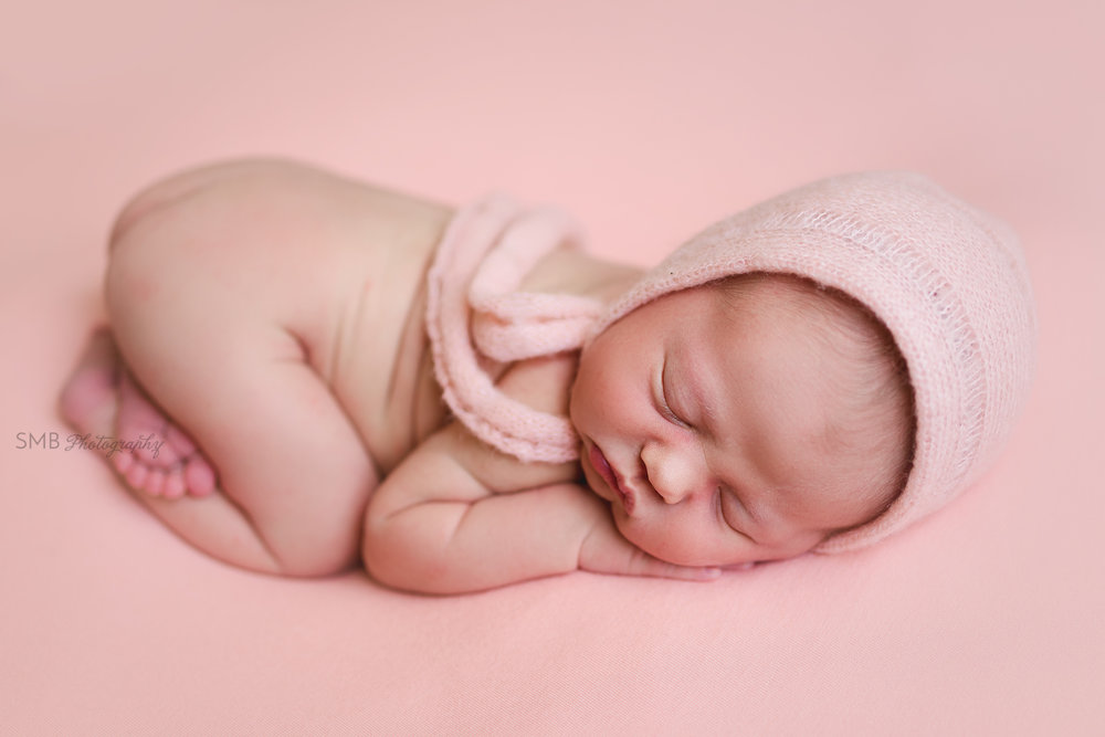 Newborn girl sleeping on her stomach with hand under her cheek
