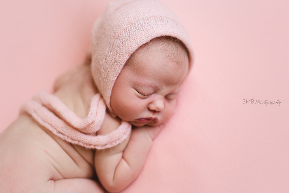 Profile portrait of baby girl wearing peach bonnet