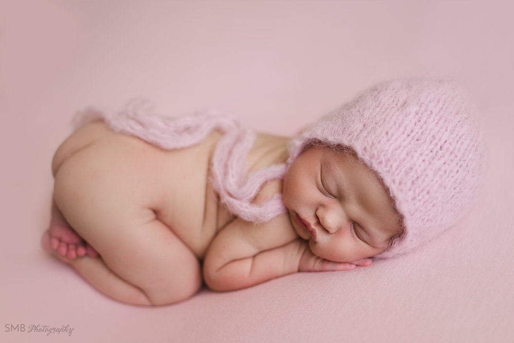 Baby girl in tooshie up pose, wearing pink fuzzy bonnet