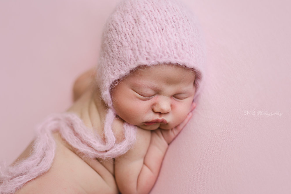 Baby girl sleeping on pink backdrop