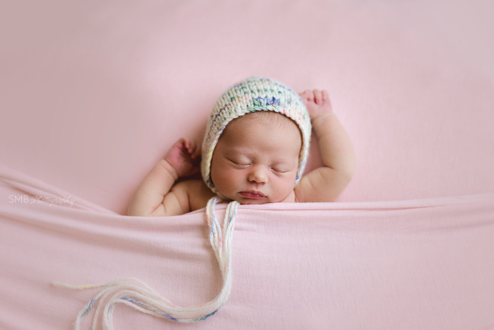 Baby girl tucked in wearing multicolored bonnet