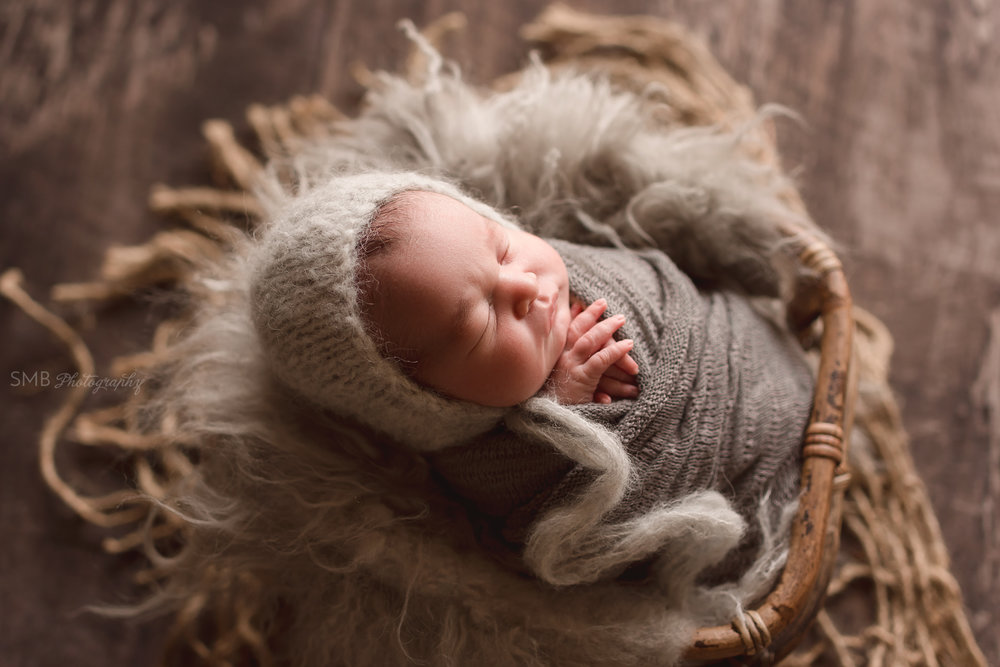 Newborn boy wrapped in basket