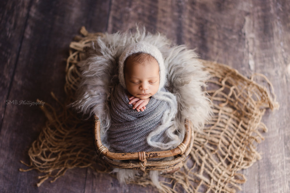 Baby boy in bamboo basket wrapped in textured gray