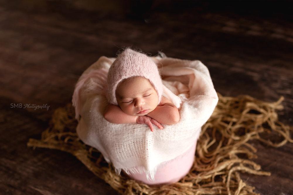 Baby girl sleeping in pink bucket