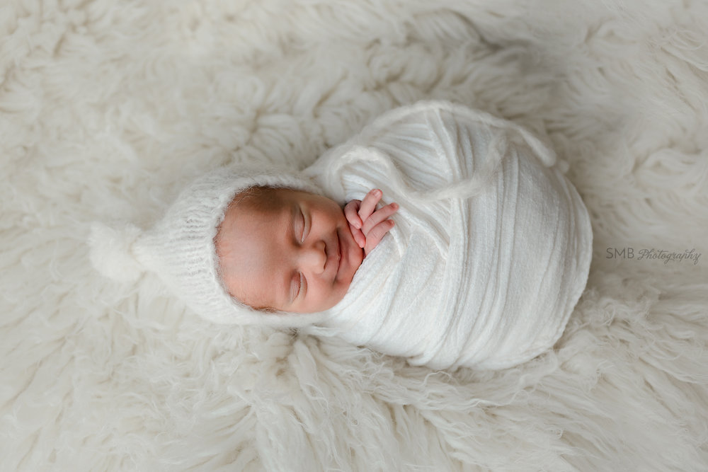 Sleeping newborn wrapped and smiling