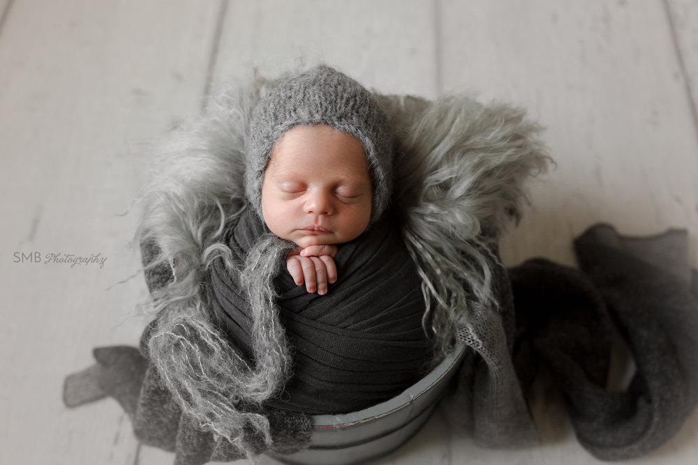 Newborn wrapped in gray wooden bucket
