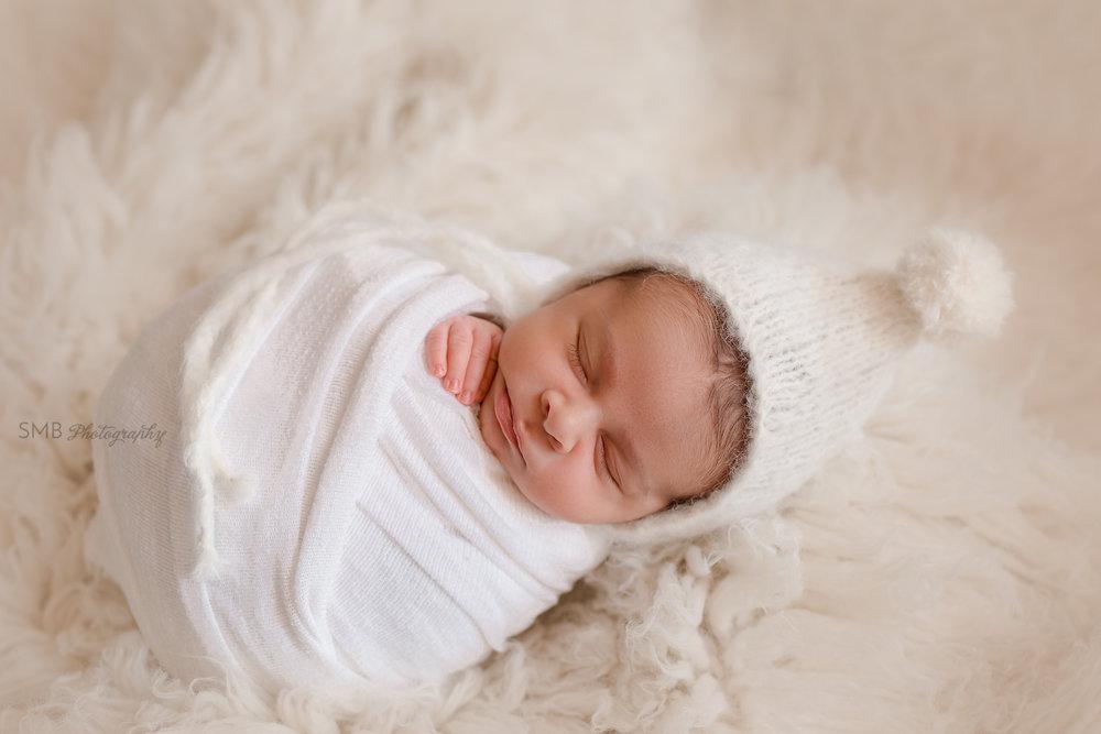 Newborn wrapped on cream wool flokati