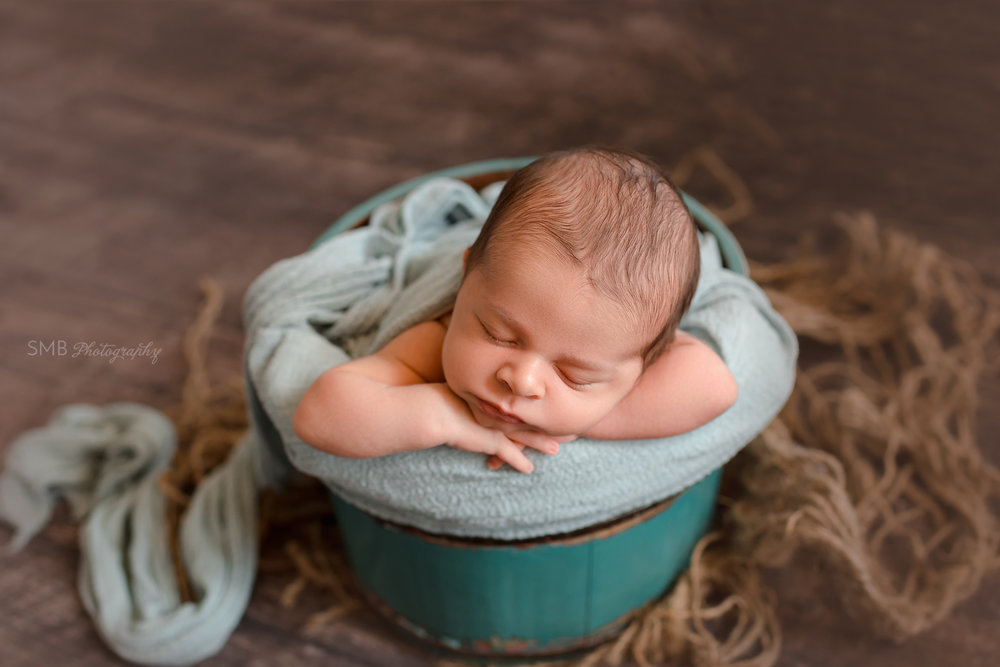 Newborn with head on hands in wood bucket