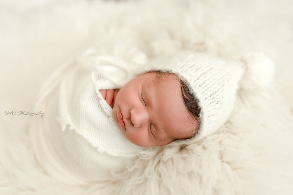Baby sleeping on side, wrapped in cream sweater