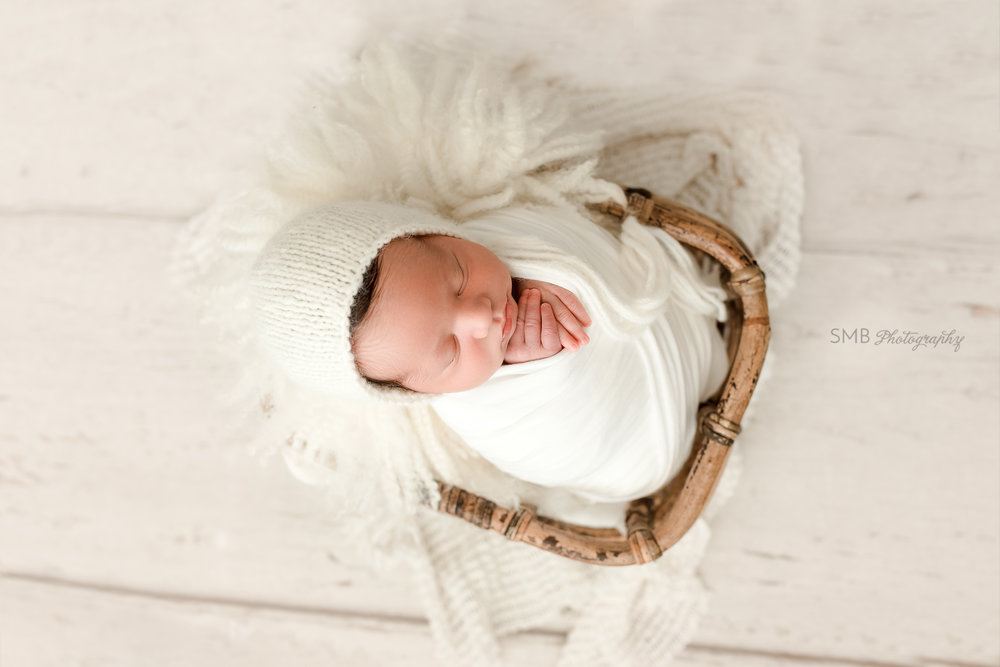Baby wearing cream bonnet in wood basket