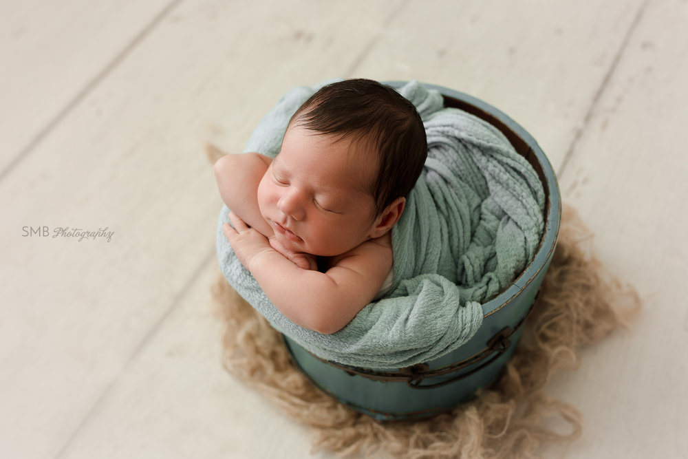 Profile of baby in wood bucket