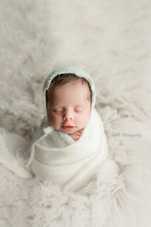 Newborn baby girl smirking on white fur