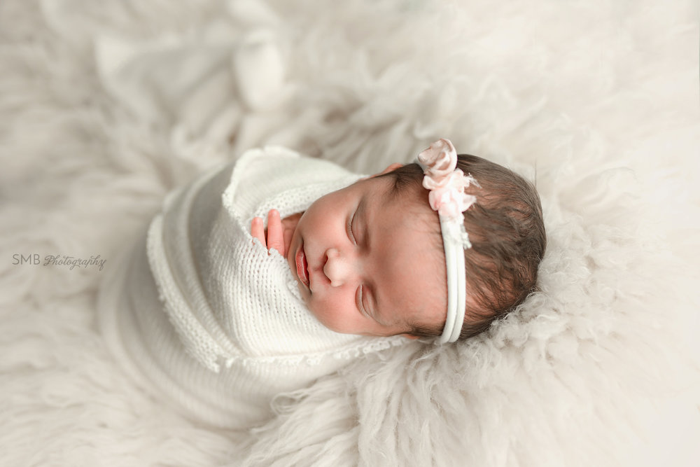Baby girl sleeping on white fur