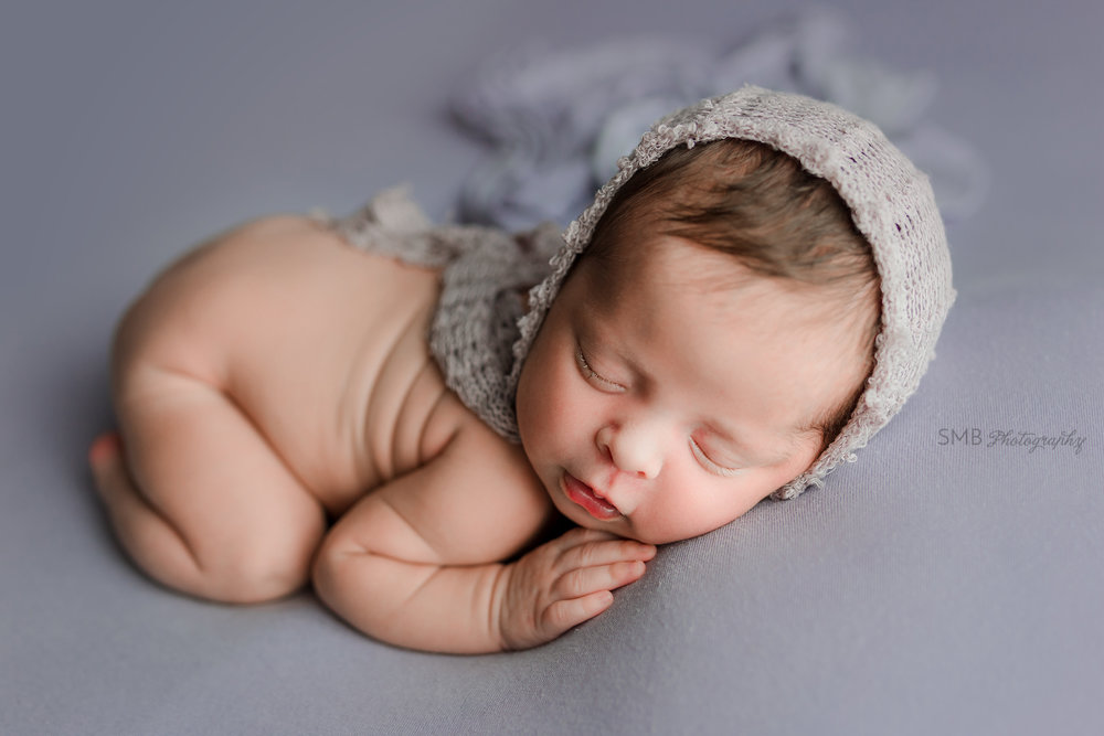 Baby girl wearing textured purple bonnet