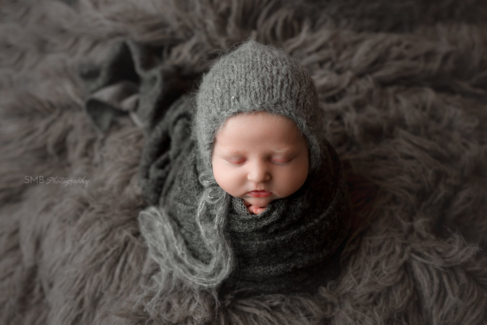 Baby girl wrapped on gray flokati