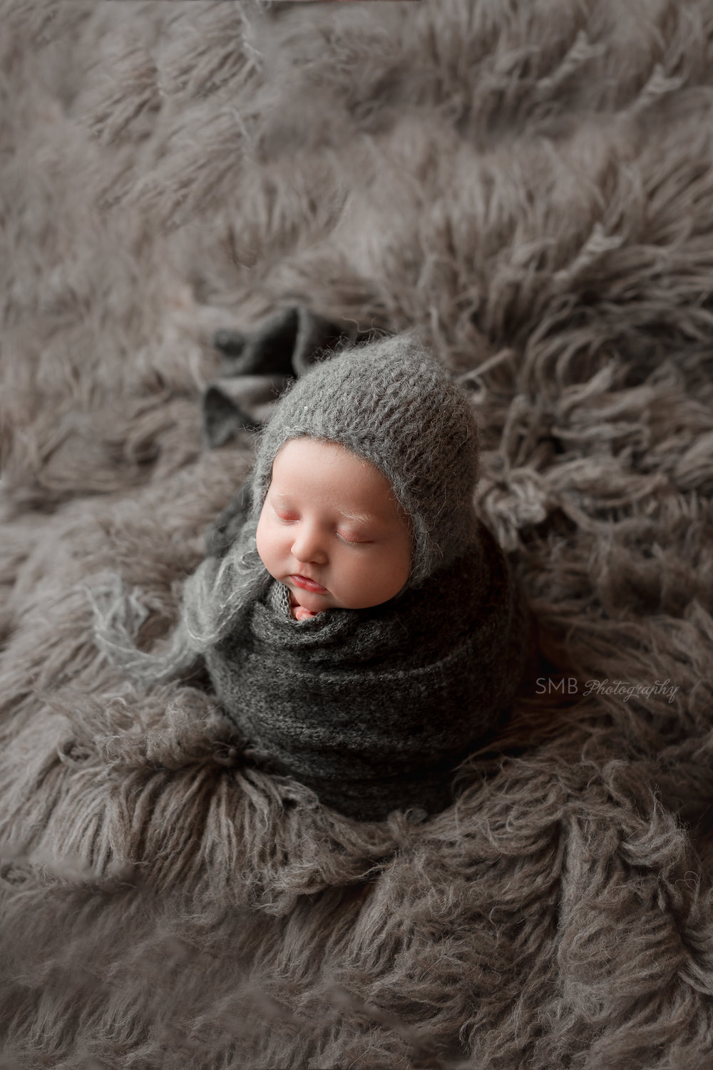 Newborn wrapped in charcoal wrap on gray fur