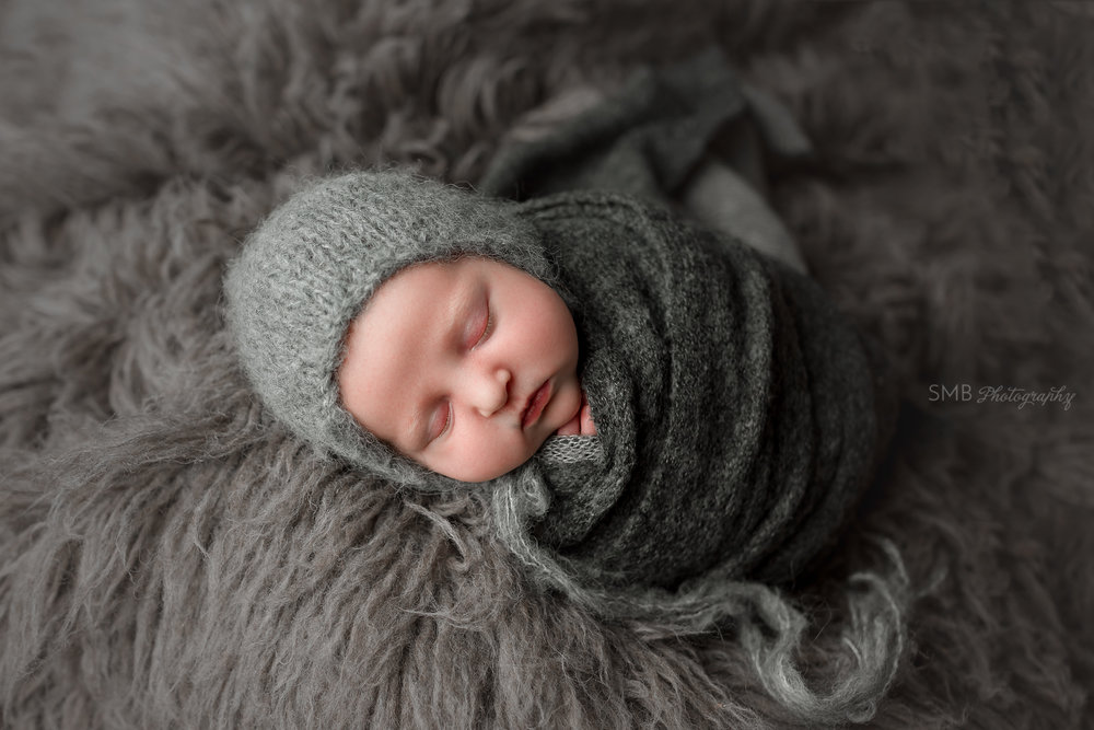 Newborn wrapped in potato sack pose