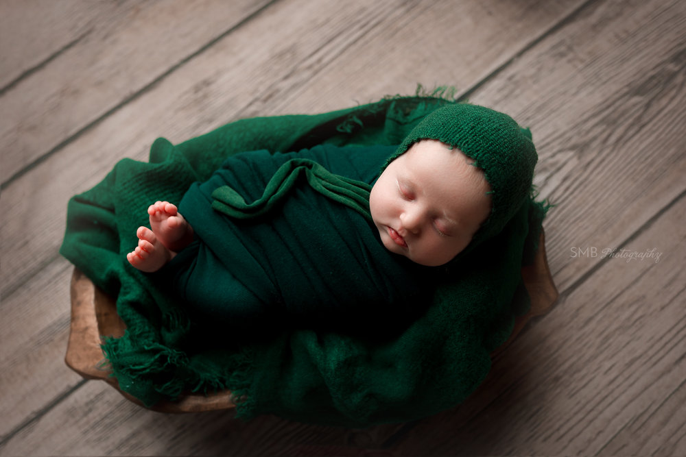 Baby wrapped up in wood trencher in hunter green