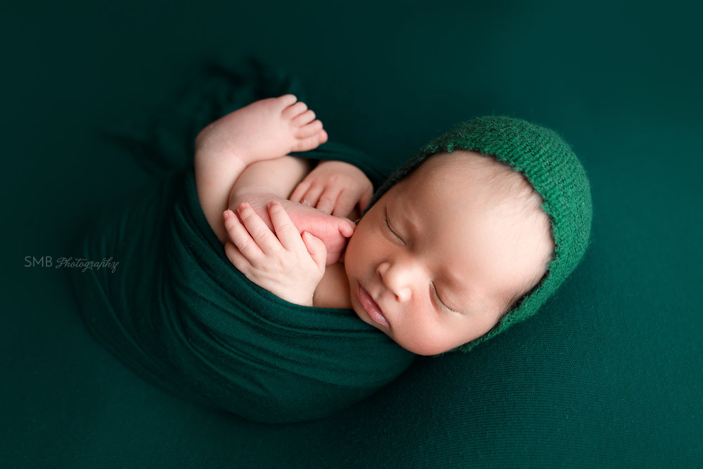 Wrapped newborn baby wearing hunter green bonnet