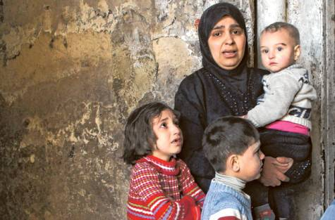 A woman and her children stand outside their home following a government air strike. The government has denied that it detains children.