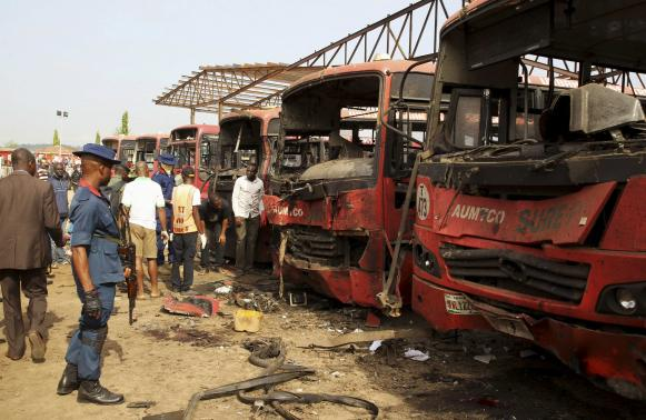 Bomb experts search for evidences in front of buses at a bomb blast scene at Nyanyan in Abuja April 14, 2014.