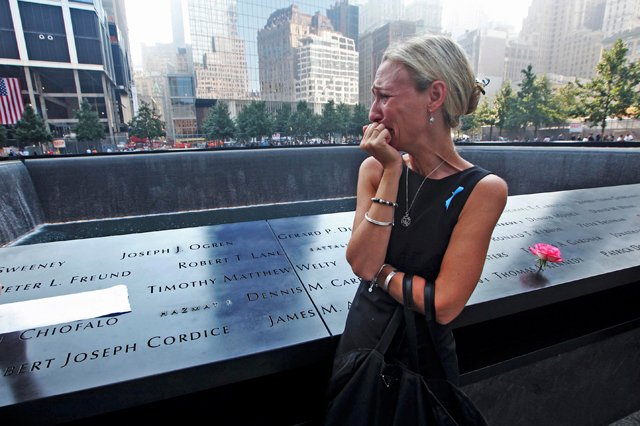 Carrie Bergonia looks over the name of her fiance, firefighter Joseph Ogren, during ceremonies at the 9/11 Memorial marking the 12th anniversary of the 9/11 attacks on the World Trade Center in New York. (Photo: © Reuters)