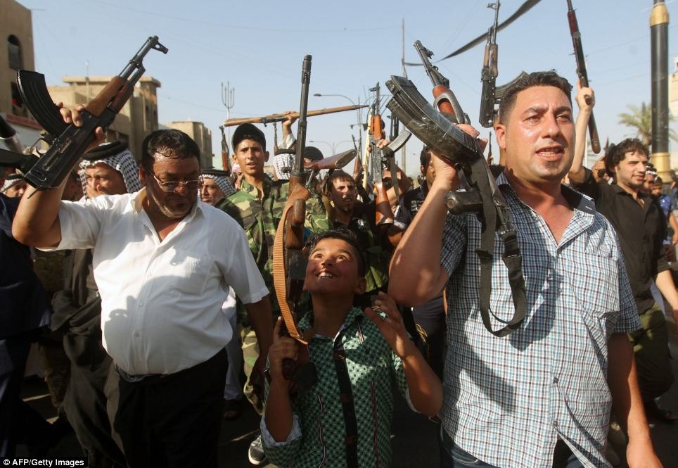 A Iraqi young boy and tribesmen hold up their weapons in the capital Baghdad today as they prepare for an ISIS attack.