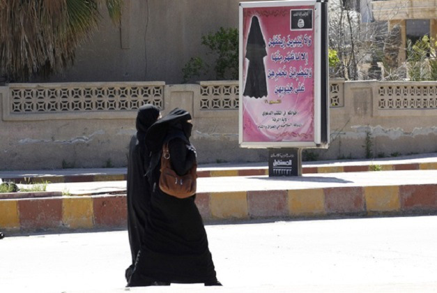 Women walk past an ISIS billboard that carries a verse from Koran urging women to wear a hijab, in the northern Syrian province of Raqqa. (Stringer/Reuters). Photo courtesy of: The Atlantic