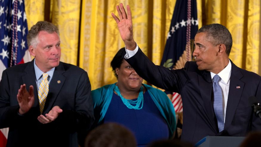 July 21, 2014: Virginia Governor Terry McAuliffe, left, applauds as President Obama waves after signing an executive order to protect LGBT employees from federal workplace discrimination in the East Room of the White House in Washington. Obama's executive order prohibits discrimination against gay and transgender workers in the federal government and its contracting agencies, without a new exemption that was requested by some religious organizations.AP Photo/Jacquelyn Martin