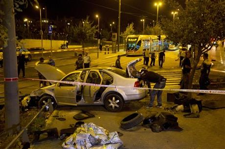 Israeli police officers inspect a car at the scene of an attack in Jerusalem, Wednesday, Oct. 22