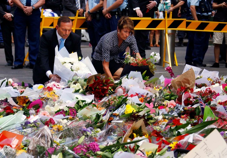 Australian Prime Minister Tony Abbott and his wife Margie place flowers at the makeshift memorial for the hostage victims of the Sydney cafe siege. (photo credit:REUTERS)