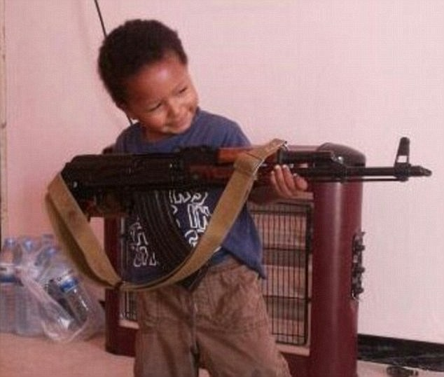 Two children have been the first to be seized from their mother as she was arrested on suspicion of terrorism offences at Luton airport last week. Above, the young son of jihadi Khadijah Dare poses with an AK-47 rifle.