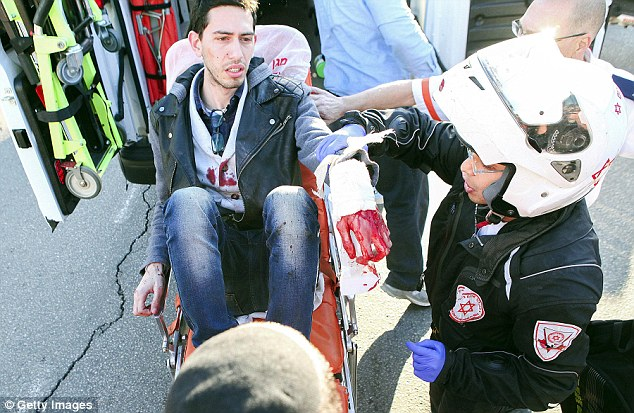 A victim of the attack, covered in blood, is treated by paramedics moments after the stabbing.