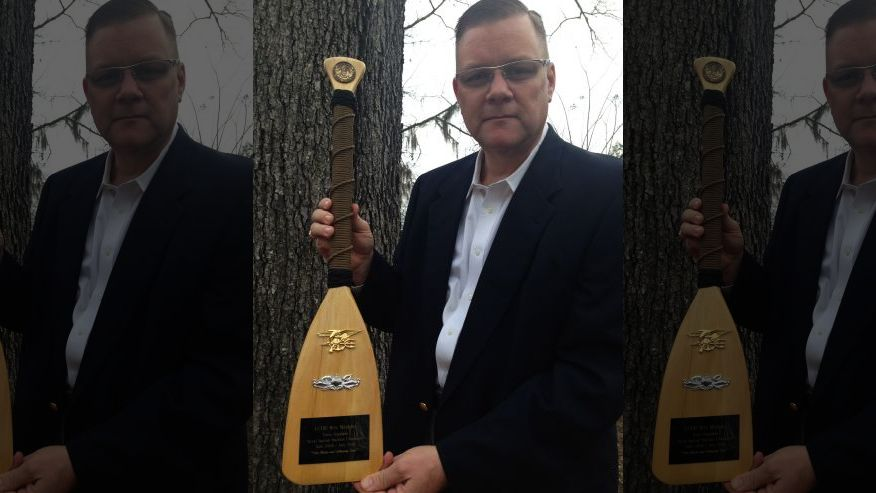 Navy Chaplain Wes Modder is pictured with a ceremonial oar presented to him by Naval Special Warfare Command. He received the oar at the end of his tour. (Courtesy Wes Modder)