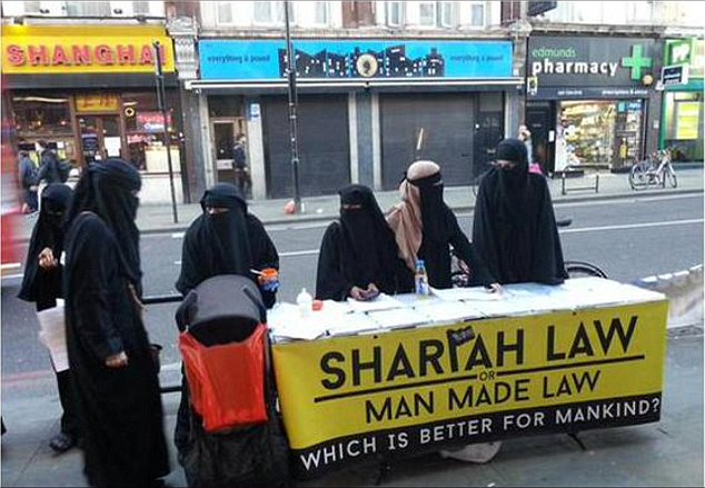 The photograph shows Muslim women, all in black burkas, running a campaign stall in Dalston, East London.