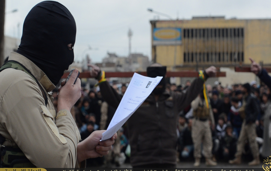 (PHOTO: SCREENGRAB/JUSTPASTE.IT) A masked ISIS militant reads the charges facing the two men tied to a cross, who were later shot in the back of thehead forbanditry, Mosul, Iraq.