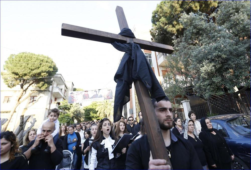 Assyrian Christians, who had fled the unrest in Syria, carry a wooden cross outside the Saint Georges Assyrian Church in Jdeideh, northeast of Beirut. Aramaic-speaking Assyrians are being driven from Syria and Iraq by war and the militant group (Anwar Amro/AFP/Getty Images).
