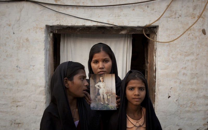 Asia Bibi's daughters pose with a photograph of their mother (Photo: CNS)