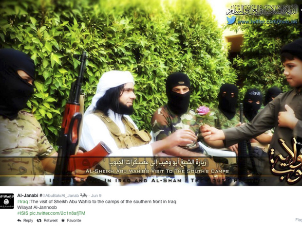 This Screen grab from an ISIL affiliated Twitter account, taken Sunday, Sept. 20, 2014, purports to show senior military commander Abu Wahib handing a flower to a child while visiting southern Iraq, as part of the group's broad social media campaign. As ISIL battles across Syria and Iraq, it is also waging an increasingly sophisticated media campaign.
