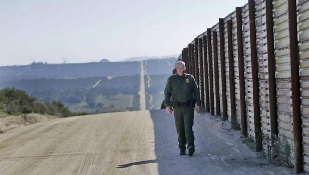 A U.S. Border Patrol officer walks along a fence on the border with Mexico recently.
