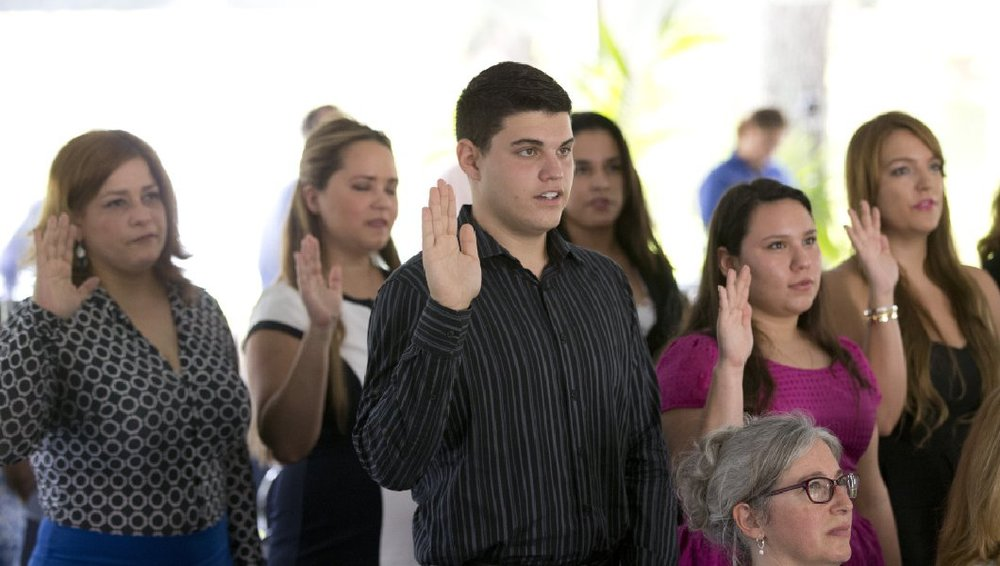 New citizens take the Oath of Allegiance during a naturalization ceremony Monday, July 6, 2015, in Miami. (AP)
