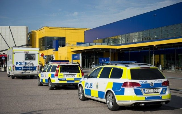 Police vehicles are lined up outside the store near Stockholm.