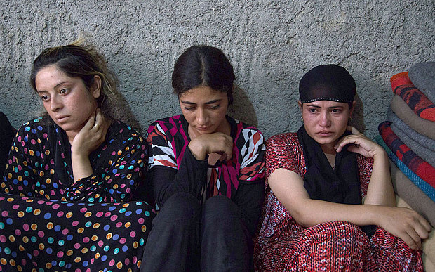 Yazidi women sit at a refugee camp recently. ISIS members using social media openly discuss their enslavement.