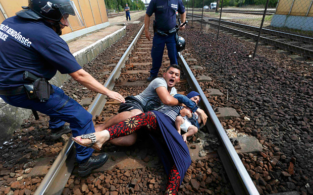 A refugee throws himself, his wife and his child down onto railroad tracks in Hungary as police try to intervene.
