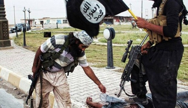 ISIS militants stand over a dead body in the Salaheddin province of Iraq.