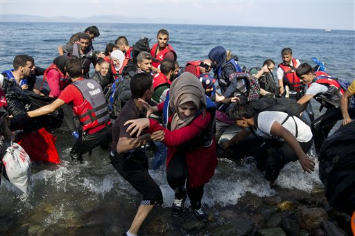 Migrants and refugees arrive on a dinghy after crossing from Turkey to Lesbos island, Greece, on Tuesday.